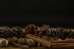 Close up of walnuts with pine cones and cinnamon stick. On wooden table Royalty Free Stock Image