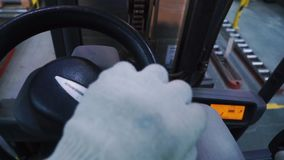 Close up warehouse worker distributing goods in a storehouse with forklift truck loader. Clip. Man driving a loading. Machine stock footage
