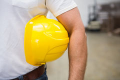 Close up of warehouse worker holding a hard hat Stock Image