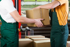 Close-up of warehouse workers with box Royalty Free Stock Photos