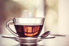 Close up the warm black tea cup on the wooden table in living Royalty Free Stock Photos