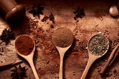 Close up of warm colorful various spices and herbs with pepper shaker. In wooden spoons on natural texture wood plate stock photo