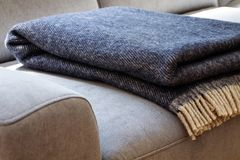 Close-up of a warm, navy blue, wool blanket with beige fringe on a comfy, gray sofa in a cozy living room interior. Concept stock images