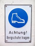 Close up of a warning sign advising people to wear mountain boots. A close up of a warning sign advising people to wear mountain boots in German which reads ` Stock Images