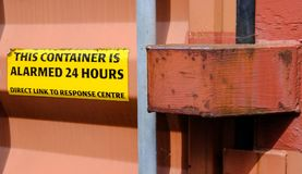 Close-up a Warning sign attached to a locked shipping container, seen at a port. The Alarmed warning sign is seen attached to one of the metal doors of this Royalty Free Stock Images