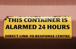 Close-up a Warning sign attached to a locked shipping container, seen at a port. royalty free stock photos