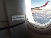 Close up warning words `Life Vest Under Your Seat` On the front passenger seat and Outside the window aircraft wing of the plane royalty free stock photos