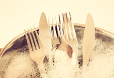 Close up of washed dishes in the kitchen: silver spoons, forks and knifes. retro filtered image Stock Image