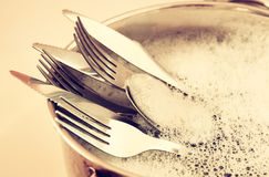 Close up of washed dishes in the kitchen: silver spoons, forks and knifes. retro filtered image Stock Images
