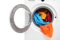Close up of a washing machine loaded with clothes royalty free stock photos