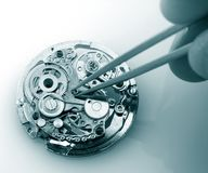 Vintage mechanical watch caliber. Close up of watchmaker repairing old mechanical watch caliber taking small piece with tweezers royalty free stock photos
