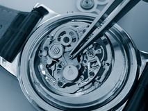 Vintage mechanical watch caliber. Close up of watchmaker repairing old mechanical watch caliber taking small piece with tweezers royalty free stock images
