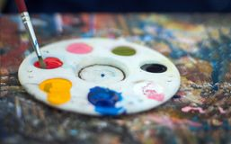 Close up water color palette and brush. On dirty table with color royalty free stock photo