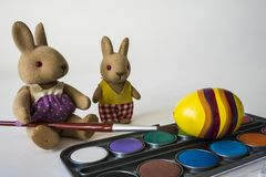 Painting Easter eggs with red brush. Yellow egg and stuffed animals on white table. royalty free stock photos