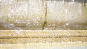 Close up of water curtain of old yellow marble fountain. Transparent water flowing. Summer sunny day.  stock footage