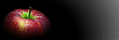 Water droplet on glossy surface of red apple on black background stock image