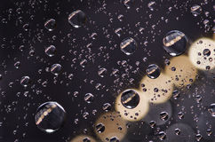 Close-up on water drops background on creamy and black surface. Stock Photos