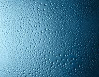 Blue gradient drops. Close-up water drops on blue gradient glass surface as background Royalty Free Stock Image