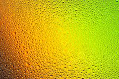 Close up of a water drops. On a yellow,orange,green  and brown gradient background, covered with drops of water -condensation Royalty Free Stock Photo