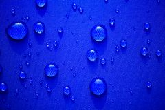 Close up Water drops pattern over a blue waterproof cloth background. World Water Day concept Royalty Free Stock Photography