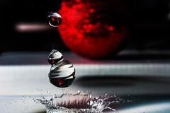 Close-up of water falling drops and splash crown from red Christmas toys. Holidays background Royalty Free Stock Photos