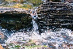 Close up of water falling through rocks on the course of a creek, California Stock Photos