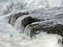 Torrents over rocks. Close up of water flowing over rocks at Ifafa beach Durban SA Stock Images