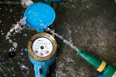 Close up water meter blue color. And a hose with flowing water. Close up water meter blue color in thailand. And a hose with flowing water stock photo