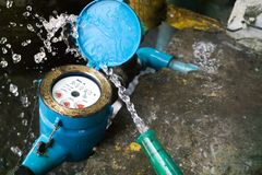 Close up water meter blue color. And a hose with flowing water. Stock Image
