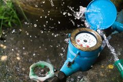 Close up water meter blue color. And a hose with flowing water. Royalty Free Stock Photos