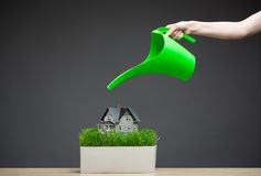 Close up of water pot pouring home model with grass Stock Image
