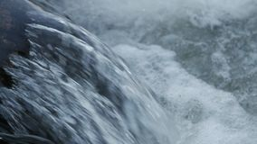 Close up of water stream with white and transparent bubbles. Slow motion stock footage