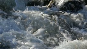 Close up of water stream with white and transparent bubbles. Zoom stock footage