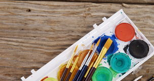 Close-up of watercolor paint box and paint brushes. On wooden table stock video footage