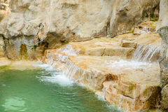 Close up of waterfall in outdoor pool at resort. Royalty Free Stock Image