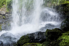 Close up waterfall surrounded with greenery. Royalty Free Stock Image