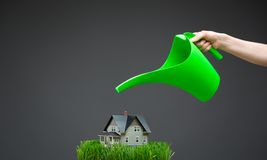 Close up of watering pot pouring home model with grass Royalty Free Stock Photography
