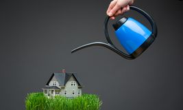 Close up of watering pot pouring house model with grass Stock Photos