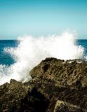 A close up of a wave crashing onto a rocky shoreline. Vertical color photo of a close up of a wave crashing onto a rocky point near Laguna Beach, California Royalty Free Stock Images