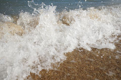 Close up wave on a sand beach, sea foam, splash of the sea Stock Photos