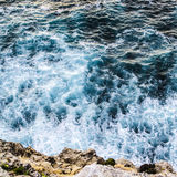Close-up of waves breaking against the cliff face in Portugal. Frothy white waves breaking against the surface of the cliff face. Blue water with the sun stock image