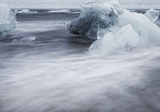 Close up of waves brushing past an iceblock Royalty Free Stock Image