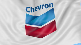 Close up of waving flag with Chevron Corporation logo, seamless loop, blue background. Editorial animation. 4K ProRes. Close up of waving flag with Chevron logo stock video footage