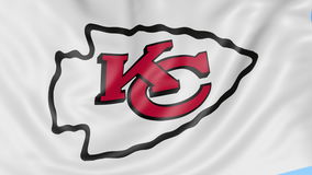 Close-up of waving flag with Kansas City Chiefs NFL American football team logo, seamless loop, blue background stock footage