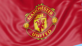 Close-up of waving flag with Manchester United F.C. football club logo, seamless loop, blue background. Editorial stock footage