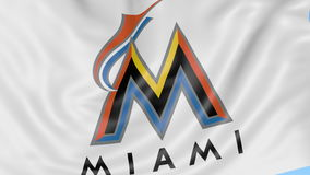 Close-up of waving flag with Miami Marlins MLB baseball team logo, seamless loop, blue background. Editorial animation stock footage
