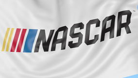 Close-up of waving flag with National Association for Stock Car Auto Racing NASCAR logo, seamless loop, blue background stock video