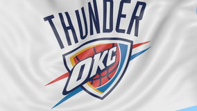 Close-up of waving flag with Oklahoma City Thunder NBA basketball team logo, seamless loop, blue background. Editorial stock video footage