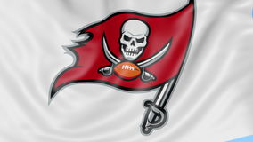 Close-up of waving flag with Tampa Bay Buccaneers NFL American football team logo, seamless loop, blue background stock footage