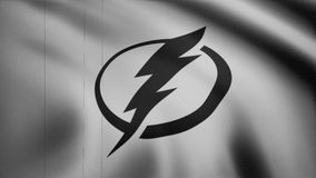 Close-up of waving flag with Tampa Bay Lightning NHL hockey team logo, monochrome, seamless loop, blue background stock footage